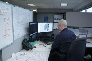 Engineer digitally modeling a transfer system.